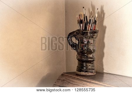 Artists paint brushes in pottery jug. Muted tones with added grain and vignetting effects.