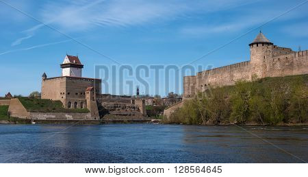 Narva Estonia - View of Herman Castle and Ivangorod Fortress on the part of the Narva River. In the distance is the spire of the town hall.