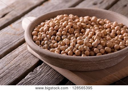 Earthen Bowl With Chickpeas On Chopping Board
