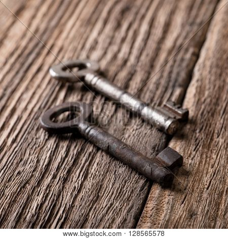 Two Keys With Worn Surface Placed On Wooden Board