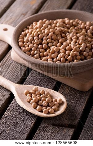 Wooden Spoon And Clay Bowl With Dry Chickpeas
