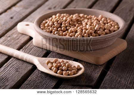Wooden Spoon In Front Of Clay Bowl Both Full Of Chickpeas