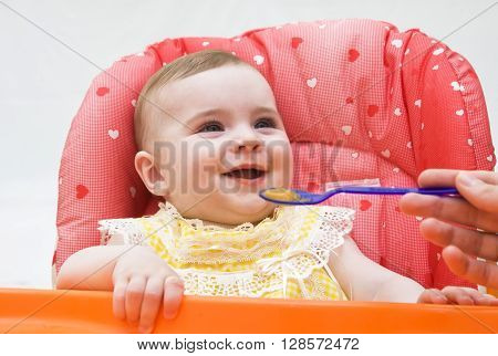 Mother feeds funny baby girl from a spoon