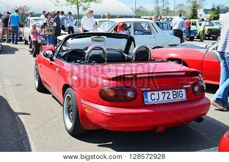 CLUJ-NAPOCA ROMANIA - APRIL 16 2016: Classic red Mazda MX-5 NA Series I (Mazda Miata) two-seat convertible roadster with retractable headlamps rear spoiler at the 2016 Retro Spring Parade.