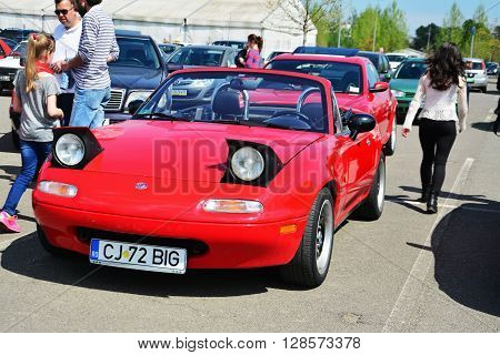 CLUJ-NAPOCA ROMANIA - APRIL 16 2016: Classic red Mazda MX-5 NA Series I (Mazda Miata) two-seat convertible roadster with retractable headlamps at the 2016 Retro Spring Parade.