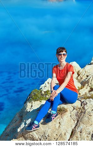 female traveler with backpack  sitting on the cliff against sea and blue sky at early morning. Balos beach on background, Crete, Greece