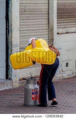 Banos De Agua Santa  - 29 November,  2014:Hispanic Sales Woman Gathering Her Products On The Streets Of Banos de Agua Santa, Ecuador, South America