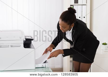 Young African Businesswoman Inserting Papers In Photocopy Machine At Office
