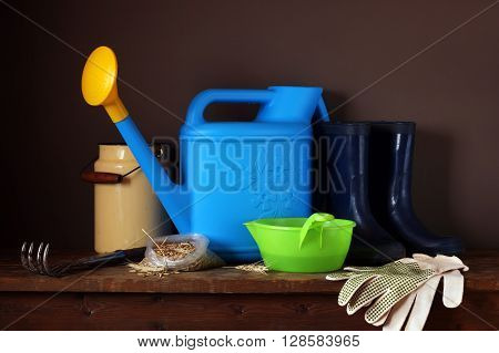 Garden tools: watering scratchy rubber boots and gloves on the table. Work in the garden the beginning of the season. Still life with corn in the package and garden equipment.