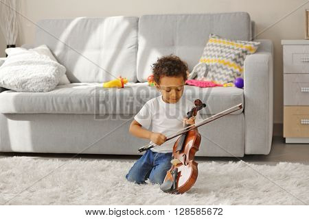 Little boy learning to play violin.
