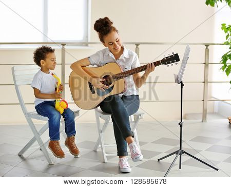 Young girl playing on guitar while little boy playing on toy saxophone