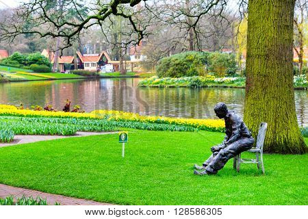 Lisse, Netherlands - April 4, 2016: Statue of man, lake, flower bed with yellow daffodil flowers in Keukenhof, Lisse, Netherlands