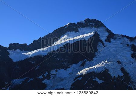 High mountain near Mount Cook. Glacier with crevasses. Evening scene.