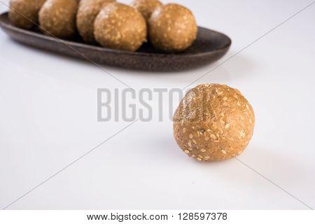 wooden plate full of tilgul laddu or til gul laddu over white background, selective focus