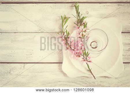 Spring table setting white plate and wine glass decorated with flowering almonds tinted