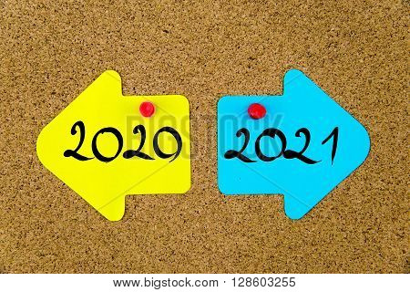 Message 2020 versus 2021 on yellow and blue paper notes as opposite arrows pinned on cork board with thumbtacks. Choice conceptual image poster