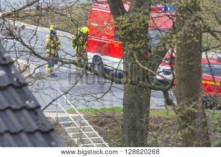 HEILIGENHAUS NRW DEUTSCHLAND - APRIL 08 2016: Firefighters in action in Heiligenhaus Germany firefighters with breathing masks before fire truck.