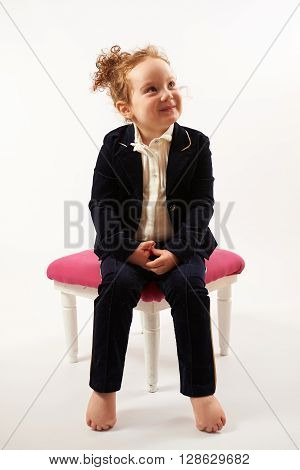 Little girl in black suit sitting on a rose stool and pouting
