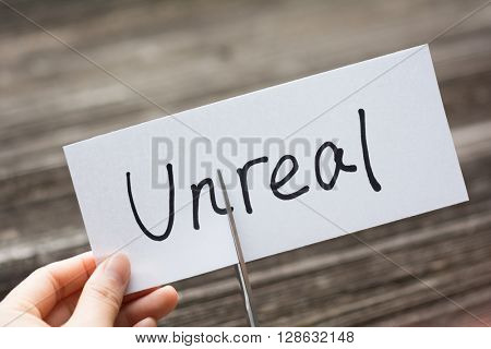 holds card with text unreal on old wood plate