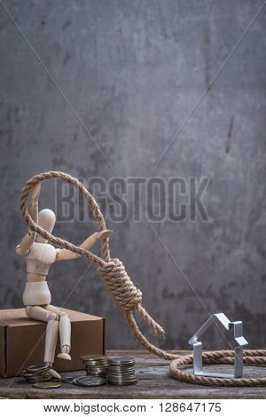 Small Wooden Dummy Sitting With Hangman's Noose, House And Coins