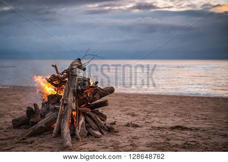 Bonfire At The Beach With Dramatic Clouds
