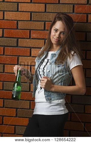 twenty something girl leaning against wall with her thumb in a beer bottle