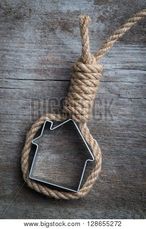 Small House Framed With Hangman's Noose Over The Old Wooden Surface