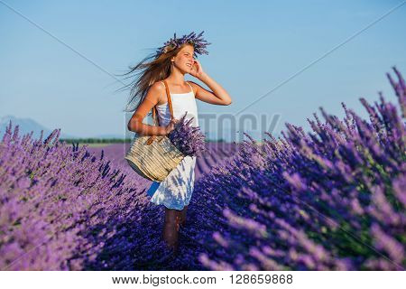 Beautiful young girl with bag and bouquet in the lavander fields in Valensole. Provence, France.