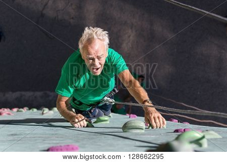Elderly Male Climber Makes Hard Move on Outdoor Climbing Wall Sporty Clothing on Fitness Training Course Intense but Positive Face Using Rope and Belaying Gear