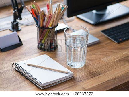 Light And Cozy Workplace With Glass Of Water