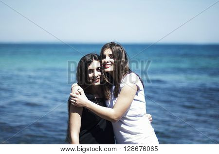 Sisters At Beach Hugging Each Other. Portrait Of Beautiful Young