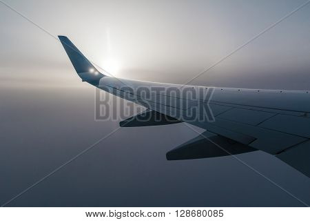 Wing of airplane and the sun shining through the fog of clouds