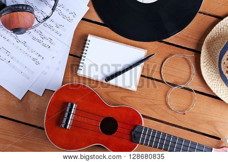 Guitar, headphones and music sheets on wooden surface, top view