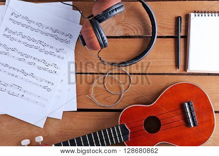 Small guitar, headphones and music sheets on wooden surface, top view