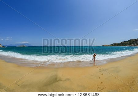 Young girl walking along golden sandy beach with white waves in a windy day with footprints in foreground and mountain Athos in background Greece Sithonia