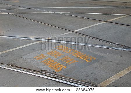 Closeup of tramway with yellow signage â??Pedestrians give way to tramsâ? in between rail tracks on concrete road in Melbourne, Australia