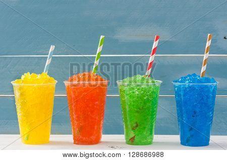 Fresh colorful summer slushies Blue wood background