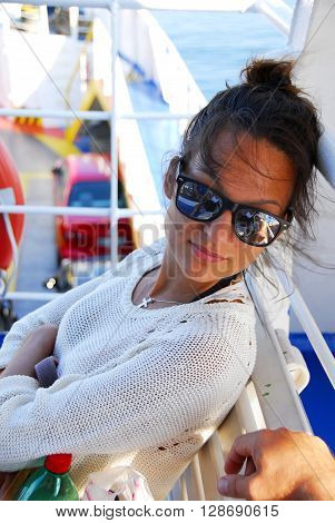 young Caucasian brunette teenage girl wearing sun-glasses traveling by ferryboat in Greece