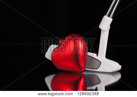 Golf putter and red heart on the black glass desk