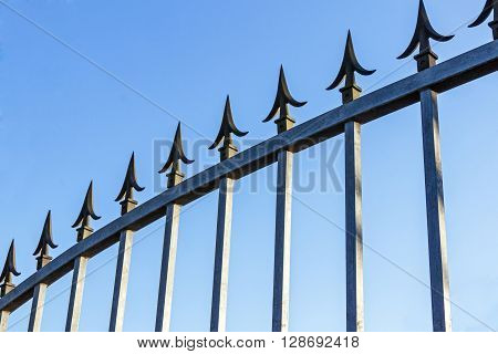 Spikes On Galvanised Gate Against Blue Sky
