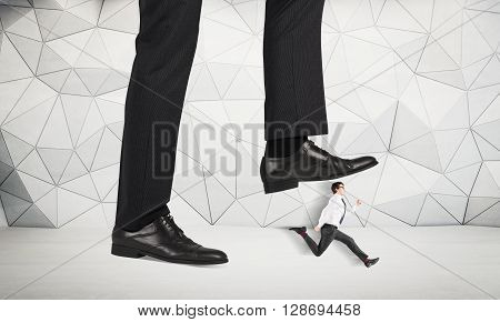 Abuse of authority concept with huge businessman foot stepping on a running male miniature with patterned concrete wall in the background