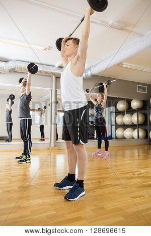 Man And Woman Exercising With Barbells In Gym