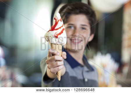 Boy Showing Ice Cream With Strawberry Syrup In Parlor