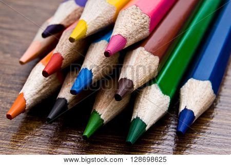 A set of colored pencils close-up on a wooden table