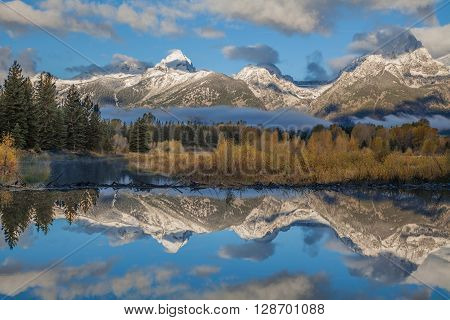 sunrise fall reflection of the snow covered tetons in wyoming