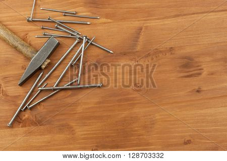 Old hammer and nails, piles of various sizes. Vintage old hammer with rusty nails. Tools on a wooden background.