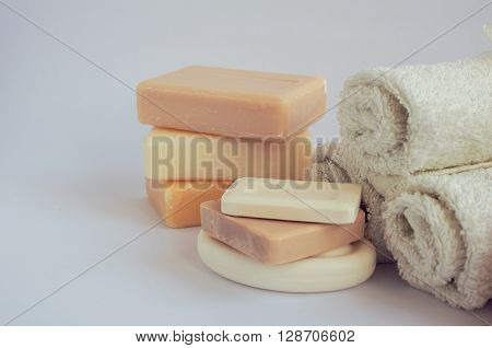 Spa setting with different kind of natural soaps and towels in pastel colors on white background. Bar of natural handmade soap. Tower stack of different handmade soaps on white. Selective focus.