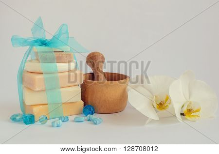 Spa setting in pastel and blue colors with different kind of natural handmade soaps orchid and the wooden pounder on white background. Selective focus. Copy space.