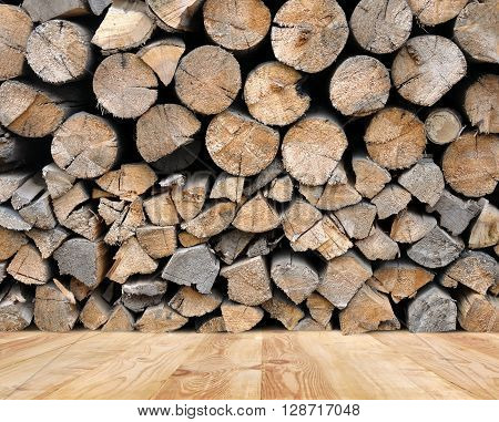 Split logs stacked in a woodpile on a wooden floor