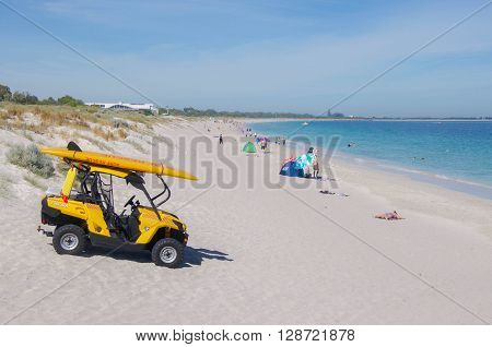 COOGEE,WA,AUSTRALIA-APRIL 3,2016: Surf lifesaving vehicle and tourists on the beach with the Indian Ocean waters in Coogee, Western Australia.